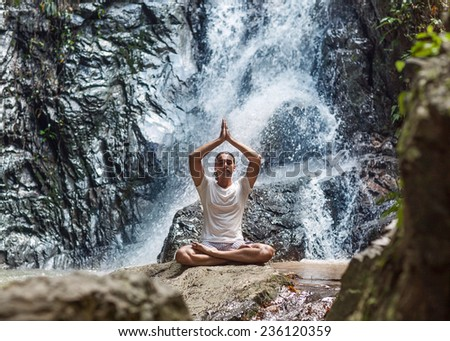 a young man engaged to a waterfall in the mountains of yoga - stock photo