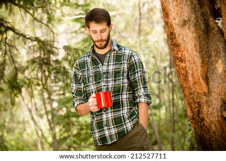 A young man enjoying a hot cup of coffee outside on a camping trip. - stock photo