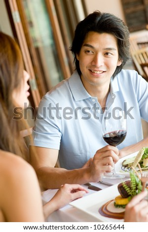 A young man enjoying wine with his meal - stock photo