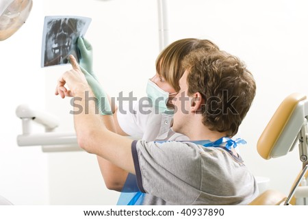 A  young man examining a panoramic radiography with his dentist. - stock photo