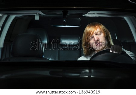 A young man exhausted and falling asleep while driving his car at night - stock photo