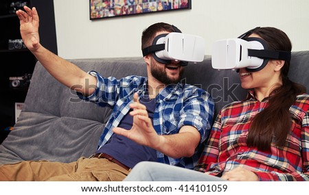 A young man explaining something to woman in virtual reality glasses - stock photo