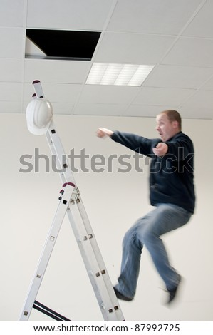 a young man falls from ladder - stock photo