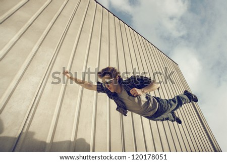A young man feels like a superhero, flying free. - stock photo