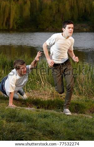 A young man fell in running next to his friend - stock photo