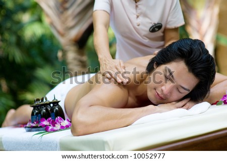 A young man getting a massage outside at a tropical spa