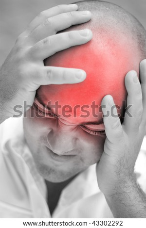 A young man grips his head in agony.  The red highlighted area illustrates his head pain. - stock photo