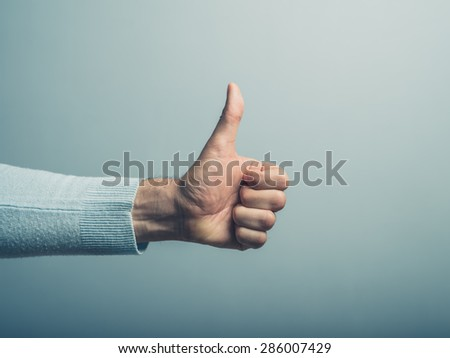 A young man' hand is displaying a thumbs up, indicating that he likes or approves of something - stock photo