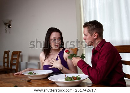 A young man handing a red rose to his girlfriend - stock photo