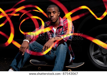 A young man hanging out seated on his skateboard with abstract light trails glowing around him and through his fingers. - stock photo