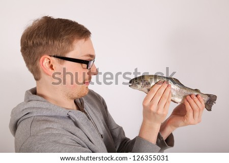 A young man has a fish in his hand - stock photo