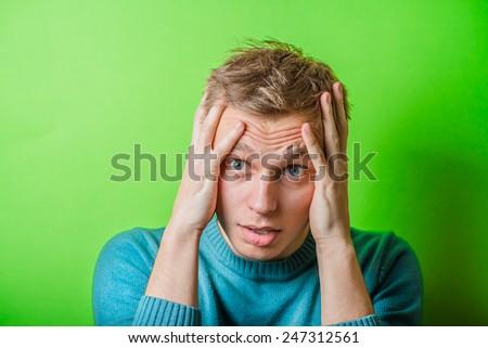 A young man having a headache - stock photo