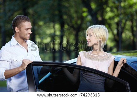 A young man helps a girl get in the car - stock photo