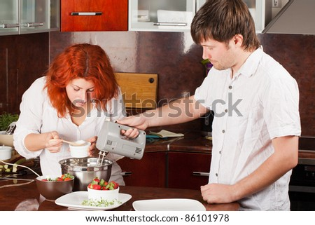 A young man helps his girlfriend in making pastry