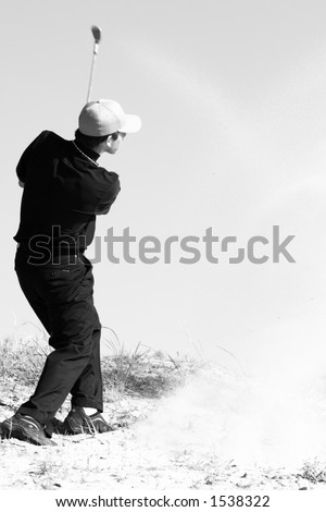 A young man hits a golf ball out of the sand (motion blur) - stock photo