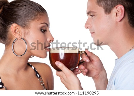 A young man holding a large cup and going to treat a beautiful woman to tea - stock photo