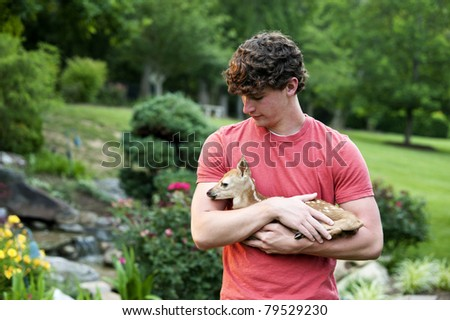 A young man holding a newborn fawn outdoors in late afternoon with landscaped background, shallow depth of field - stock photo