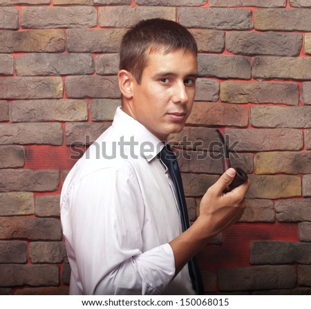 A young man holding a pipe. Smokes. - stock photo