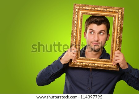 A Young Man Holding And Looking Through Frame On Green Background