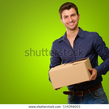 A Young Man Holding Cardboard Box On Green Background - stock photo