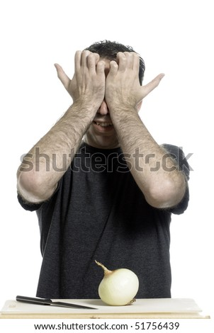 A young man holding his eyes in pain without even starting to cut the onion, isolated against a white background