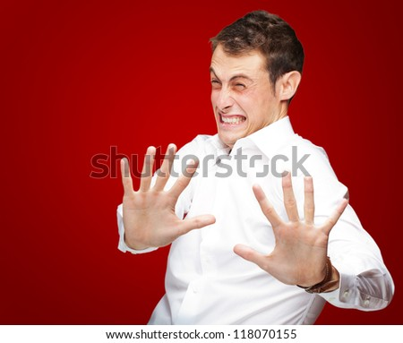A Young Man Holding His Hands Out In Fear On Red Background - stock photo