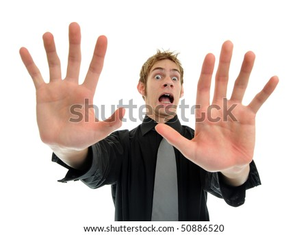 A young man holding his hands out in fear screaming for his life - stock photo