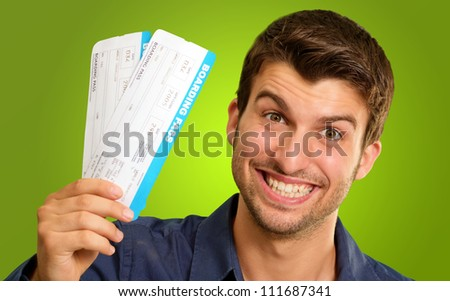 A Young Man Holding Tickets On Green Background