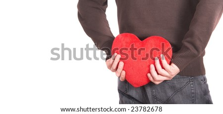 A young man holds a heart shaped pillow behind his back which he gives as a present to his girlfriend for valentines day. Isolated over white. Lot of white copyspace left.