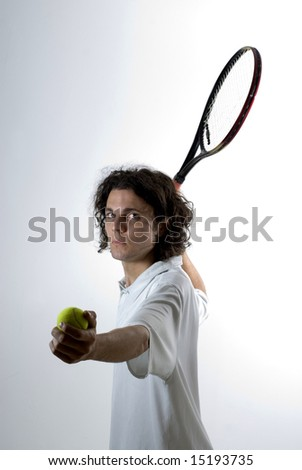 A young man, holds a tennis racket back and a ball forward, getting ready to serve the ball. He stares at the camera. Vertically framed shot. - stock photo