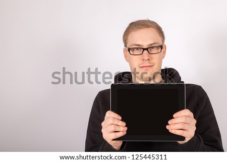 A young man holds his tablet computer in the camera - stock photo
