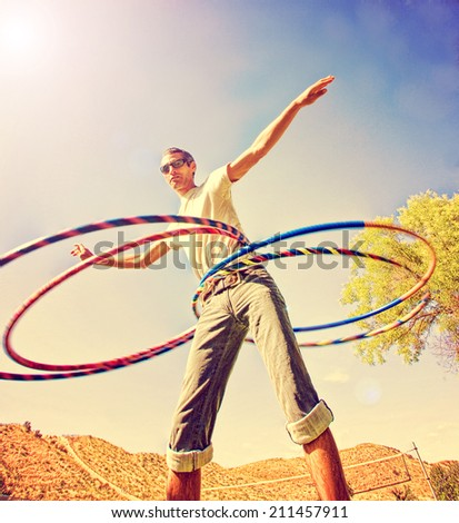 a young man hula hooping in a local park toned with a retro vintage instagram filter - stock photo