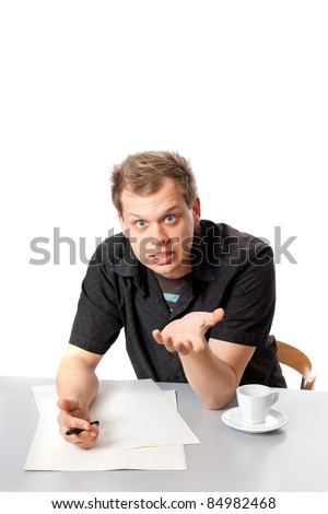 A young man in a black shirt sitting at a table and vigorously talking to you posing in studio isolated on a white background - stock photo