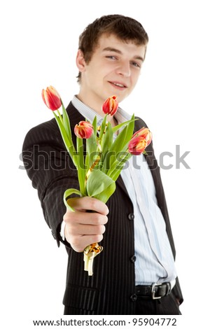 A young man in a black suit with five red tulips - stock photo