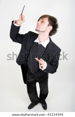 A young man in a black tailcoat is holding the stick up and is looking away, top view - stock photo