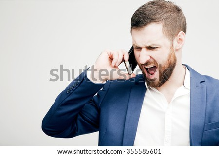 A young man in a business suit aggressively talking on the phone