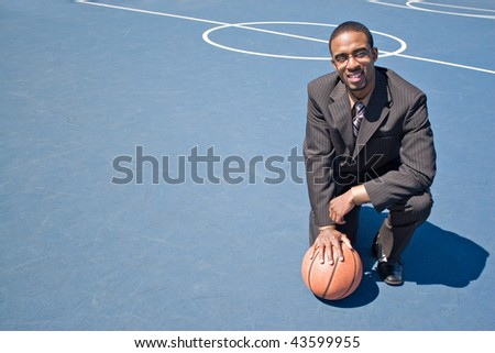 A young man in a business suit posing in the empty basketball court with lots of copyspace. - stock photo