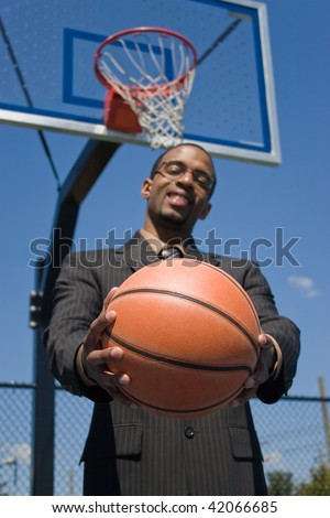 A young man in a business suit posing with a basketball.  He could be a coach player recruiter scout or trainer. Shallow depth of field with focus on the ball. - stock photo