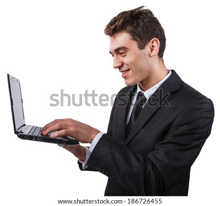 a young man in a business suit smiling to something on his laptop computer - stock photo