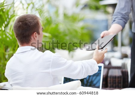 A young man in a cafe waiter takes account - stock photo