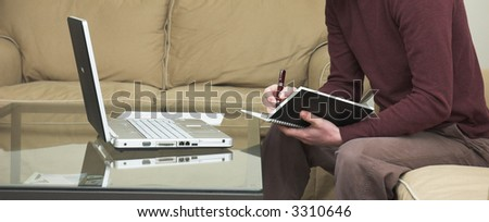 A young man in a casual contemporary setting working on a laptop computer. - stock photo