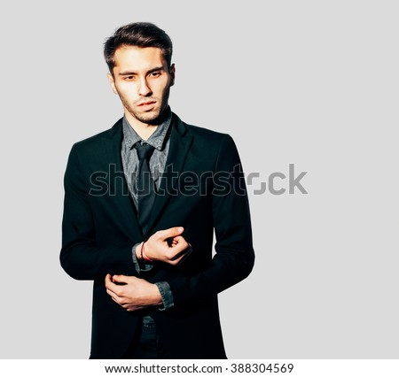 A young man in a fashionable suit posing on grey background. Indoor. Warm color.