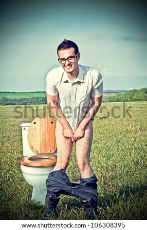 A young man in a field near the toilet