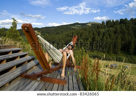 A young man in a hat relaxes in a hammock on a wooden deck in a rural setting during summer. - stock photo