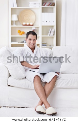 A young man in a robe with a laptop at home - stock photo