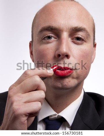 A young man in a suit applies bright red lipstick to his lips like in a mirror. - stock photo