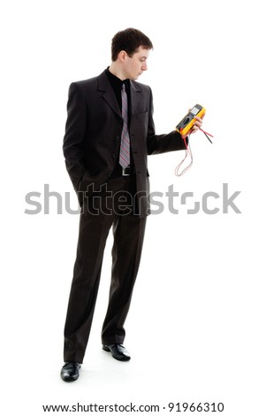 A young man in a suit, looks at the testimony of a multimeter, isolated on a white background. - stock photo