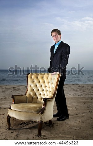 A young man in a suit on the beach with a vintage chair.