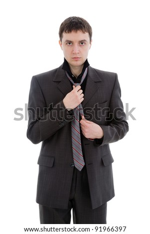 A young man in a suit, tie a tie, isolated on a white background.