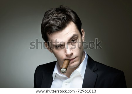 A young man in a suit with a cigar expressing doubt or skepticism - stock photo